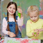 Cheerful girl and her friend playing with green slime